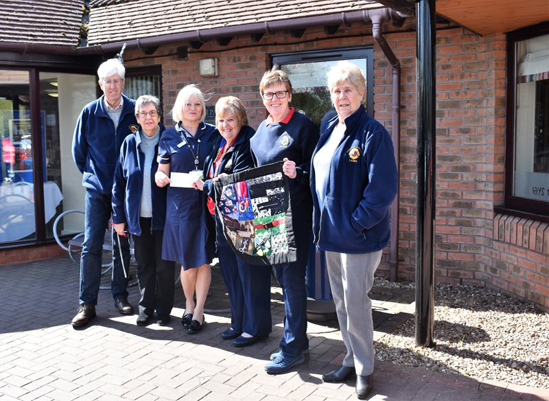 President of Winterton and District Lions Club Pauline Hollingworth (third from right) and Club member Jean Wain (second right) are pictured with other Club members presenting the cheque for £1,000 and the fidget muff to Senior Nurse Inpatient Unit Karen Andrew (third left) of Lindsey Lodge Hospice.